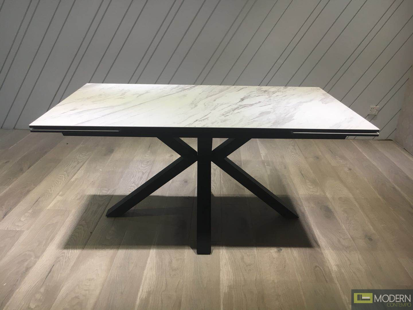 Faux marble glass-top dining table featuring a black matte X-base design and two drop leaf ends